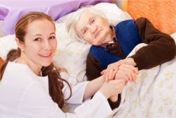 caregiver and elder holding hands