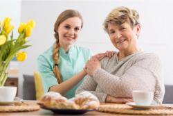 caregiver and elder holding each other